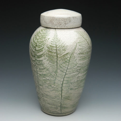 Handcrafted ceramic memorial urn with ferns