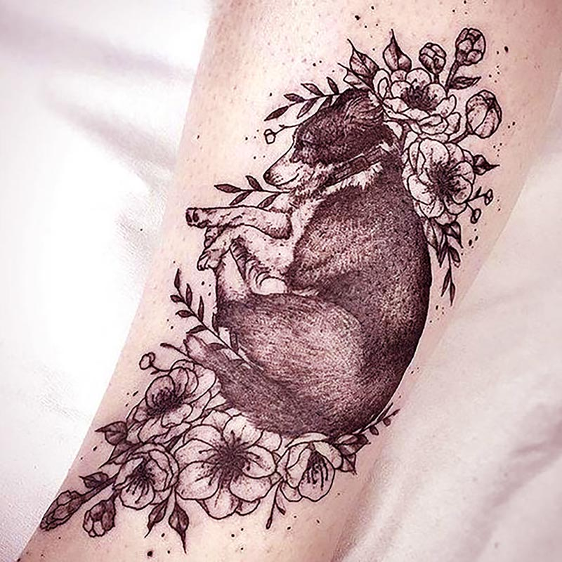 Pet dog at rest among the flowers - memorial tattoos